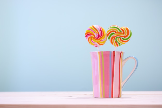 Colorful round candy and heart candy in a vertical stripes cup pastel color on wooden table