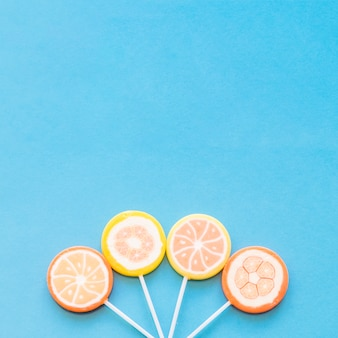 Colorful round lollipop candies arranged down over the blue background