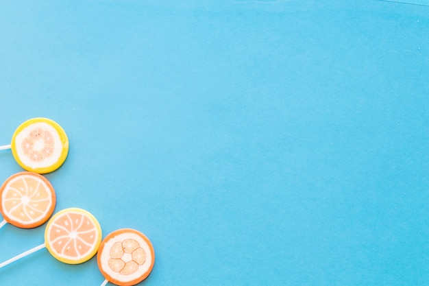 Colorful round lollipop candies on blue background
