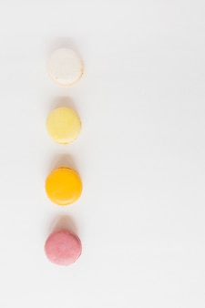 Colorful row of macaroons on white background