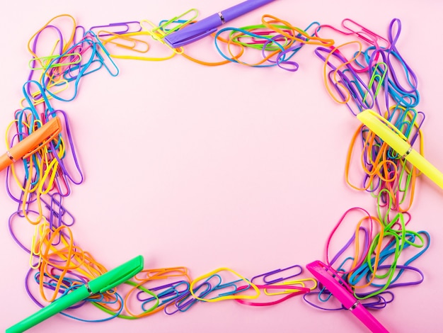 Colorful rubber bands and clip frame on pink paper