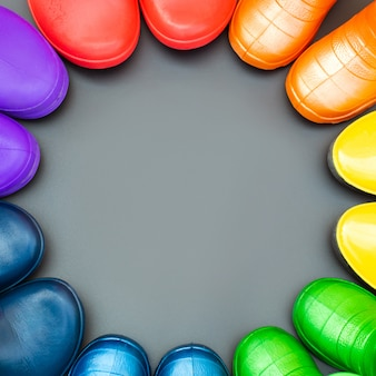 Colorful rubber boots of all colors of the rainbow stand on the gray surface in a circle. top view.