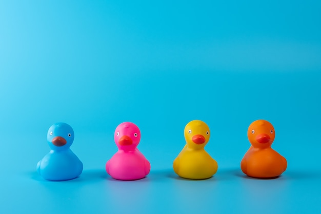 Colorful rubber ducks on blue background.