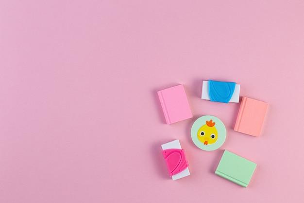 분홍색 배경에 화려한 고무 지우개입니다. 여러 가지 빛깔의 학용품. 개념 안녕하세요 9월 또는 학교, 교육으로 돌아가기. 색 배경에 학교 편지지입니다. 평평한 위치, 텍스트를 위한 공간.