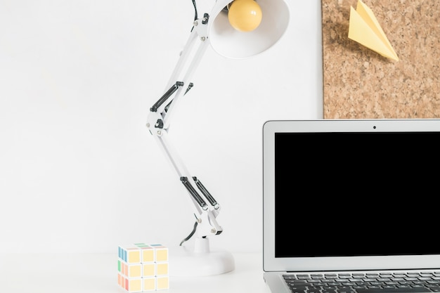 Colorful rubik cube, lamp and laptop on white desk