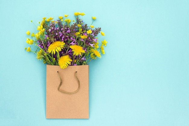 Colorful rustic flowers bouquet in craft bag