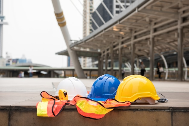Colorful safety hardhats, measure tape, and yellow worker dress on footpath with blurred modern city  background. engineering and construction equipment. engineer heavy industry project in town.