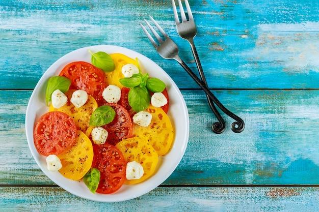 Красочный салат из помидоров, моцареллы и базилика с вилкой. вид сверху.