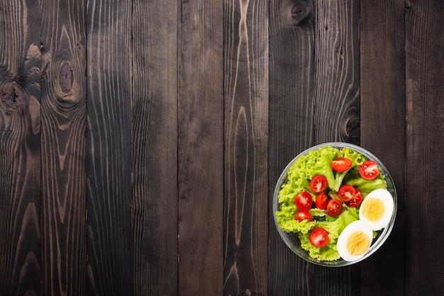 Красочный салат с помидорами, вареным яйцом и листьями салата