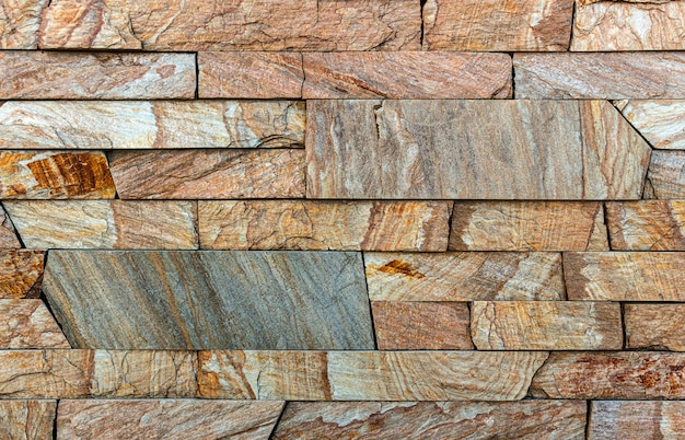 Colorful sandstone wall stone texture tile background patchwork, brown
