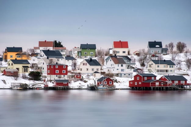 Colorful scandinavian wooden house on snowy at coastline