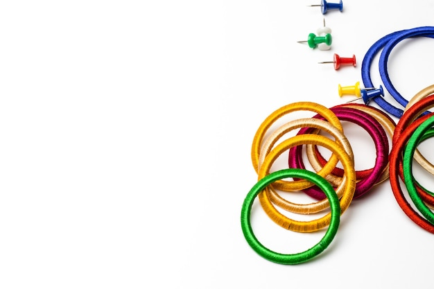 Colorful scattered bangles and paper push pins on white background with copy space