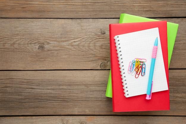 灰色の木製の背景の上にペンでカラフルな教科書