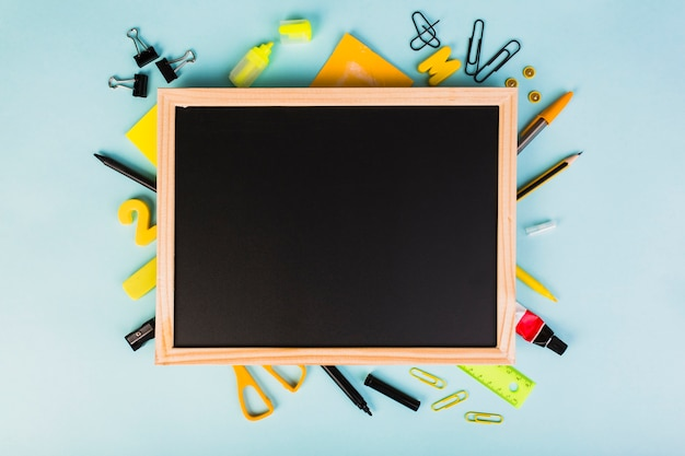 Colorful school and office supplies around chalkboard