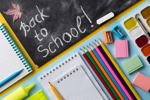 Colorful school stationery and chalkboard on colorful background.