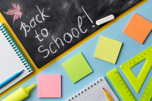 Colorful school stationery and chalkboard on colorful background