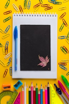 Colorful school stationery and chalkboard on yellow paper background