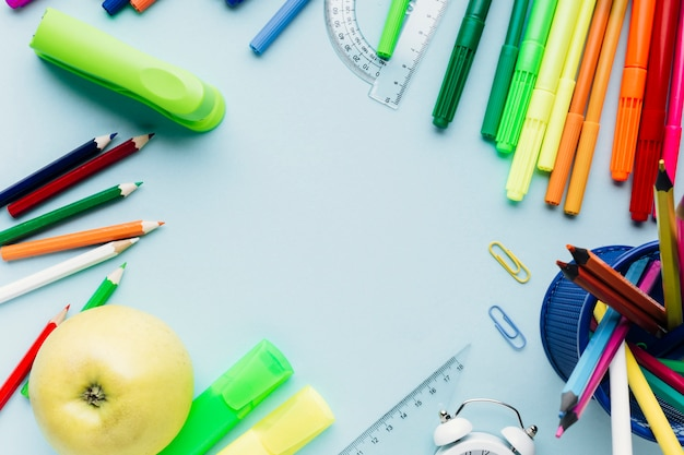 Colorful school stationery scattered around empty space on blue desk