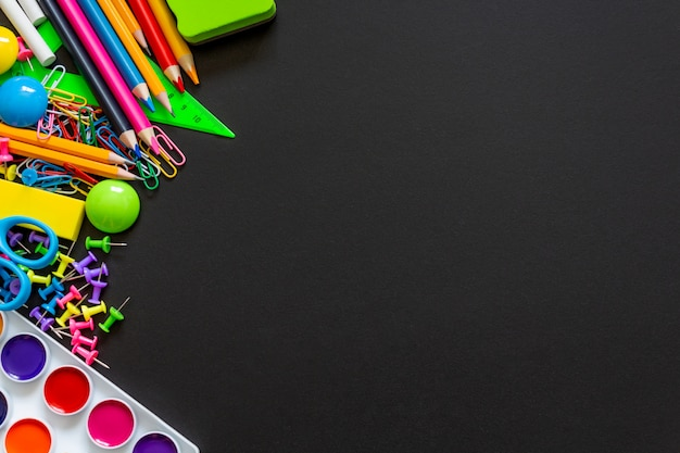 Colorful school supplies on black chalkboard background.