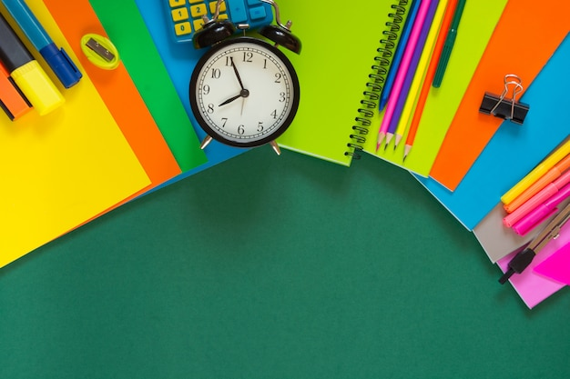 Colorful school supplies, book, and alarm clock on green.