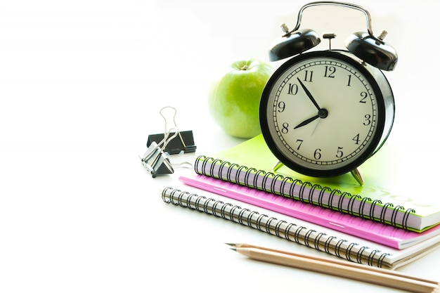 Colorful school supplies, book and alarm clock on white. close up. back to school.
