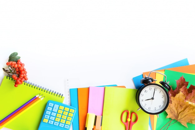Colorful school supplies, book, and alarm clock on white.