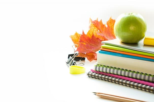 カラフルな学用品、本、白リンゴ。閉じる。学校に戻る。