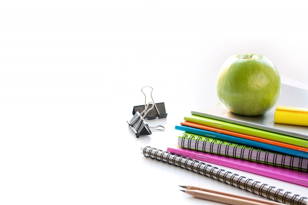 Colorful school supplies, book, apple on white. close up. back to school.