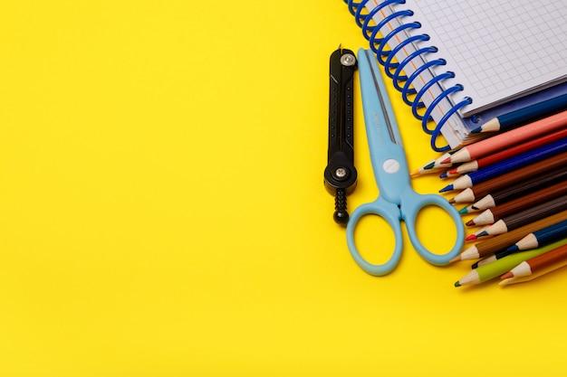 Красочные школьные принадлежности границы на линованной бумаги стол