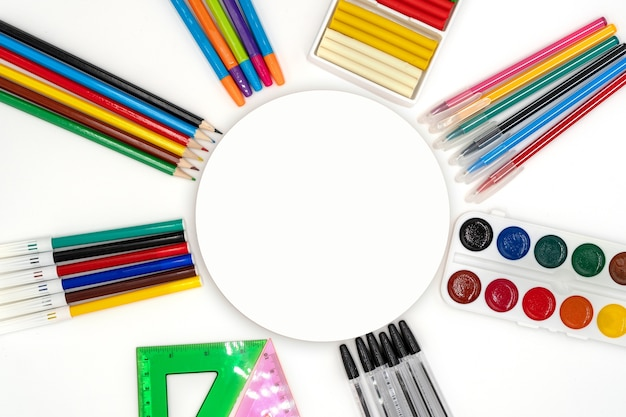 Colorful school supplies in circle arrangement on white background