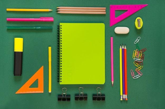 Colorful school supplies, green book on green.