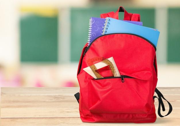 Красочные школьные принадлежности в рюкзаке на фоне доски