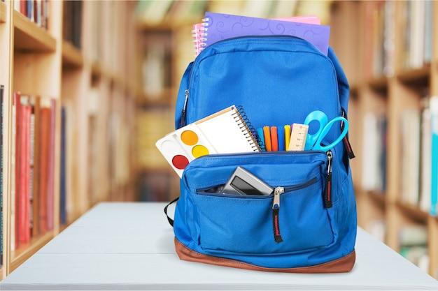 Красочные школьные принадлежности в рюкзаке на фоне класса