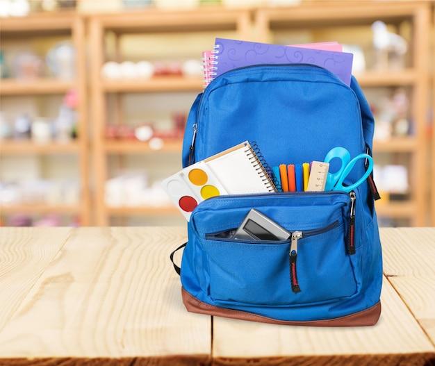 Красочные школьные принадлежности в рюкзаке на деревянных фоне