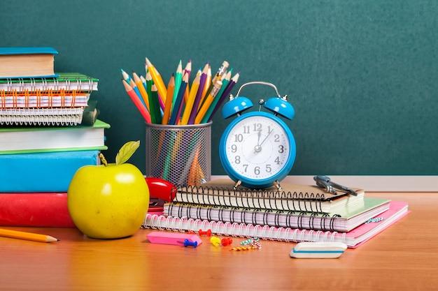 Красочные школьные принадлежности на фоне доски