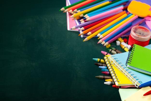Красочные школьные принадлежности на деревянных фоне