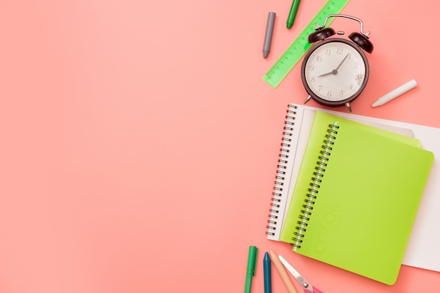 Colorful school supplies on pastel pink.