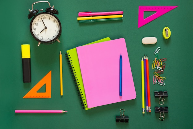 Colorful school supplies, pink book and alarm clock on green. top view