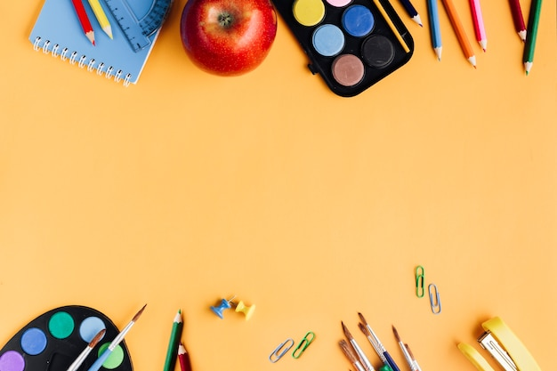 Colorful school supplies placed on yellow background