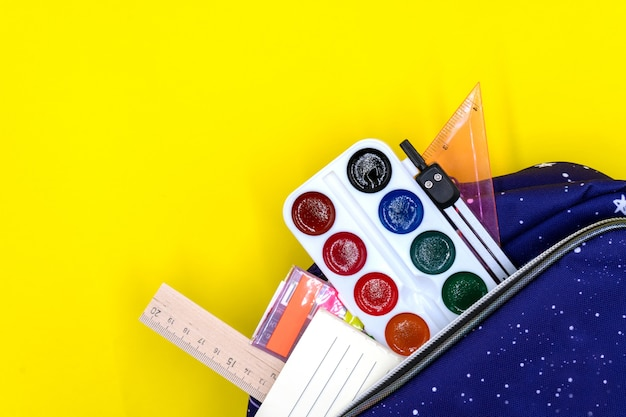 Colorful school supplies in a school backpack on a yellow background, back to school concept.