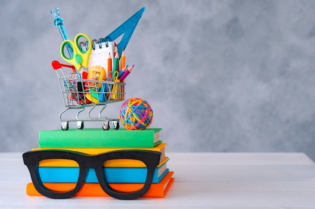 Colorful school supplies shopping basket gray background with a copy text space a stack of books wit...