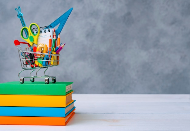 Colorful school supplies in the shopping basket on a gray background with a copy of the text space a...