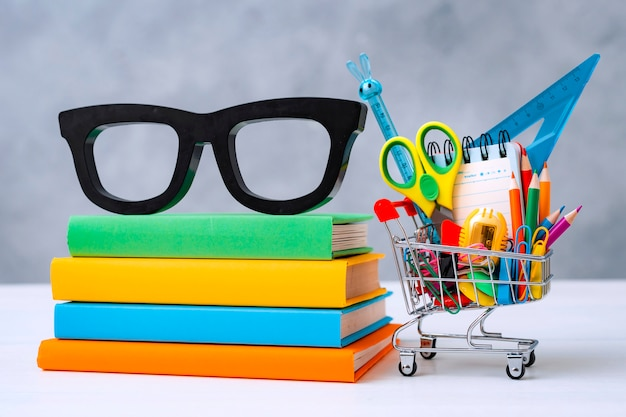 Colorful school supplies shopping basket gray  with a copy text space.