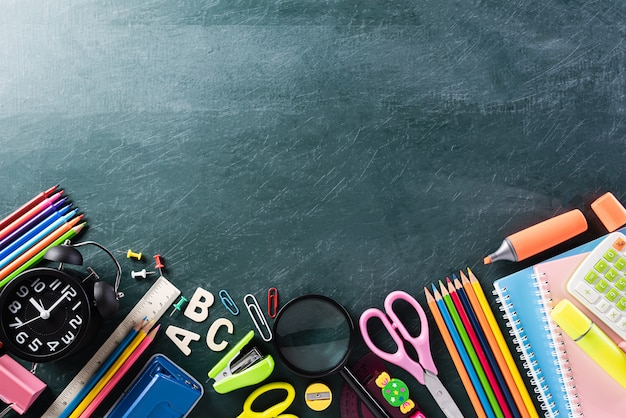 Colorful school supplies, stationary on chalk board.