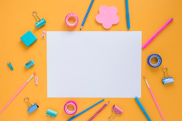 Colorful school supplies with blank paper in center
