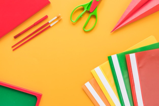 Colorful school supplies on yellow background