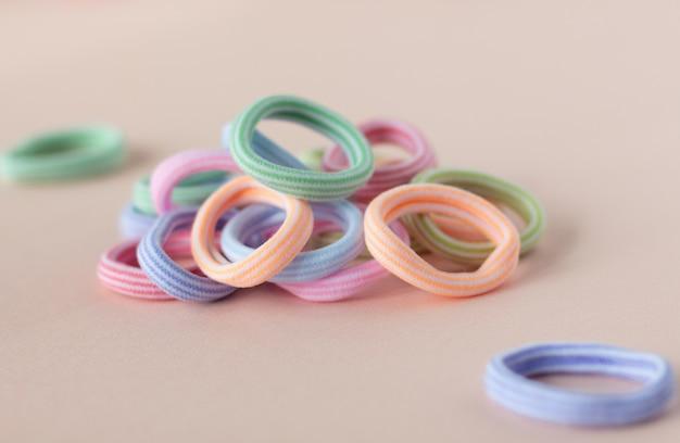 Разноцветные резинки для волос на мягком бежевом столе