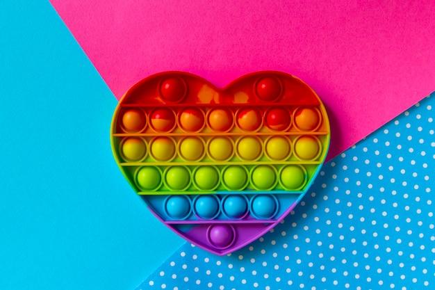Красочная сенсорная игрушка fidget push pop it heart на разноцветном фоне