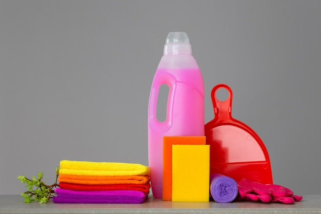 Красочный набор инструментов для уборки дома и веточек с зелеными листьями на нейтральной поверхности.