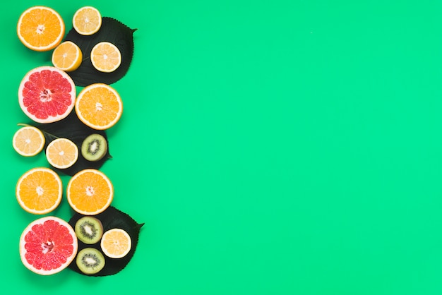 Colorful set of sliced fresh exotic tropical fruits on green background